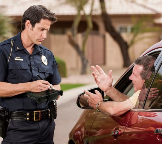 A law enforcement officer with a ticket book stands by the side of a vehicle he has stopped, as the motorist pleads his case and trys to explain why he shouldn't receive a citation or moving violation.